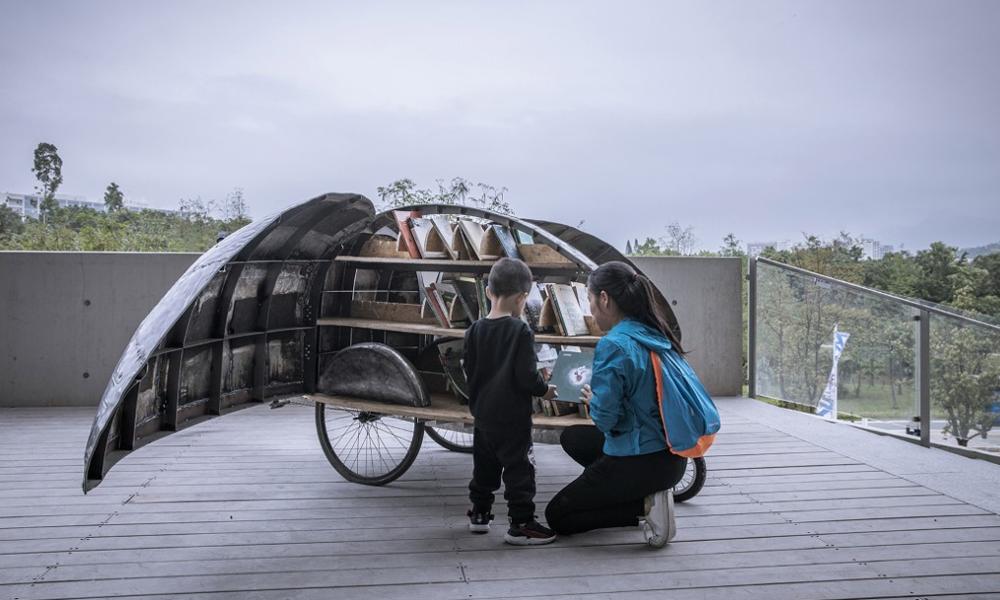 Cette caravane pour vélo cache la plus petite des bibliothèques